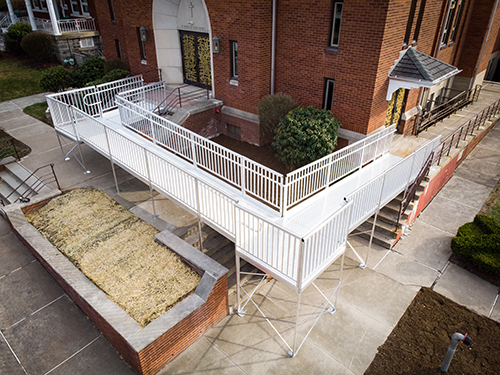 An overhead view of an aluminum commercial ramp installed outside of a school building.