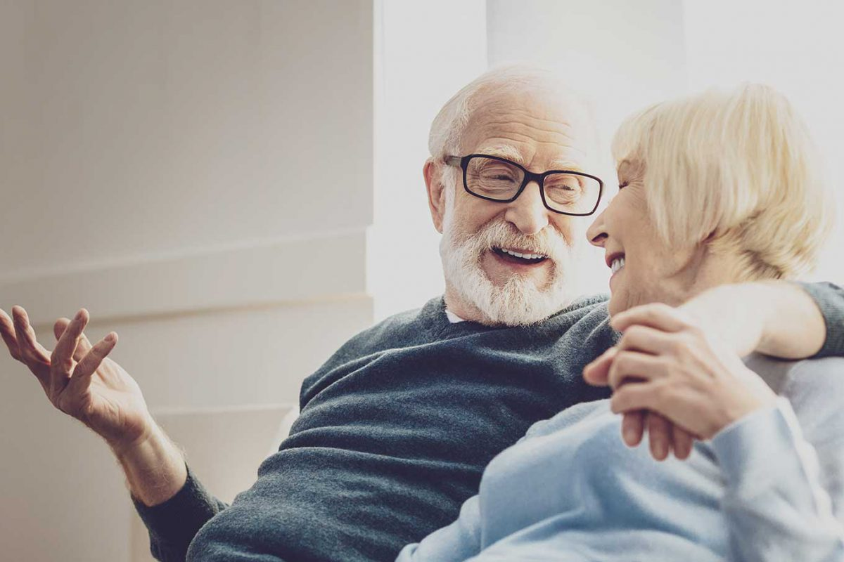 Two senior citizens siting on a couch, looking at each other and laughing. The man has his arm around the woman's shoulders, where they are holding hands.