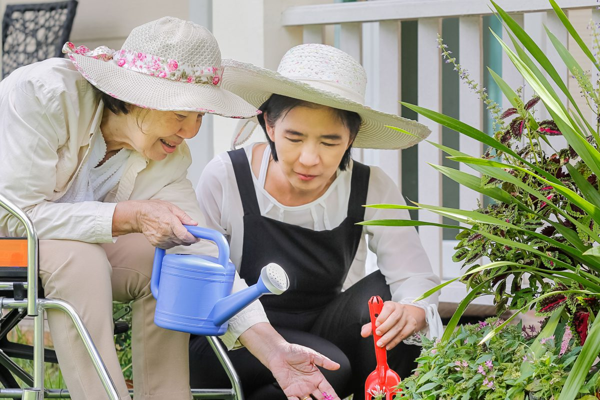 A senior citizen sits in her wheelchair with a watering can outside in her garden. She is being assisted by a younger woman in caring for the plants.