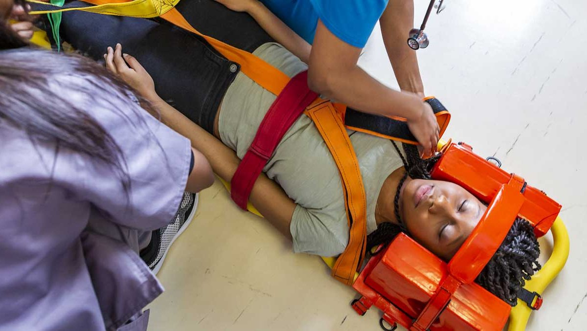 A person lying on the floor on a gurney with a neck support, being treated by EMTs.