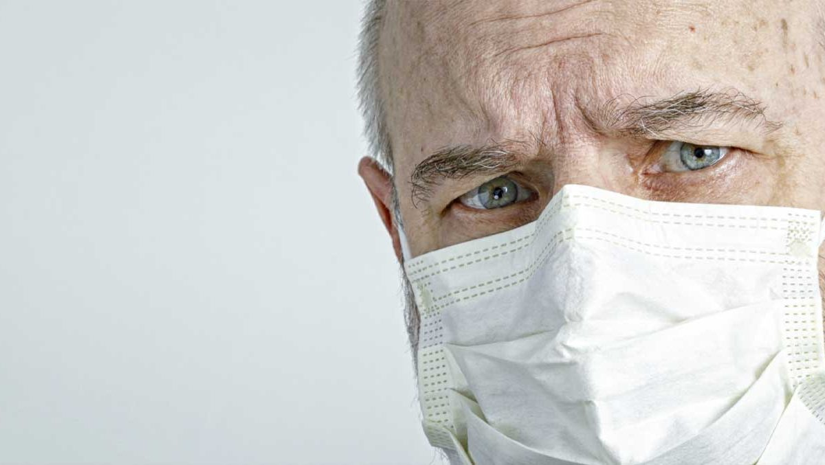 An older man looks directly into the camera. He is wearing a white, protective face mask.