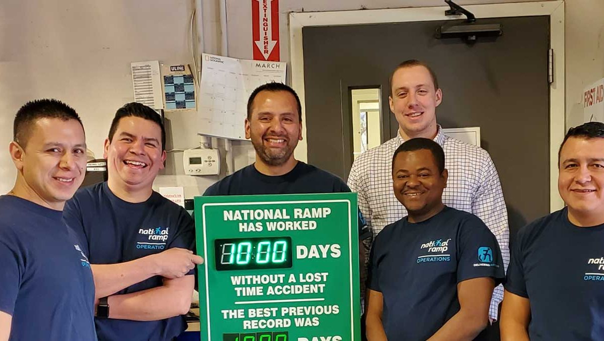 An image of the National Ramp Operations team standing in front of a sign announcing there have been 1,000 days without a loss of work accident.