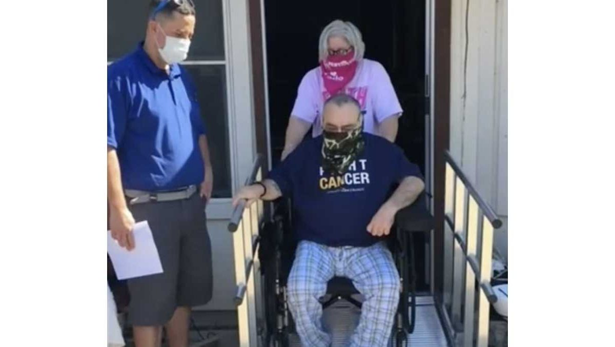 Image of a man in a manual wheelchair being pushed onto his new aluminum residential ramp by his wife, while a National Ramp dealer looks on.