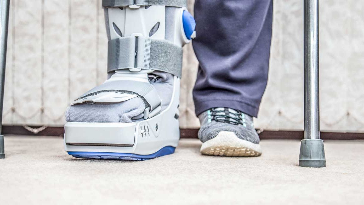 Close of up a person's feet. One foot is wearing a sneaker, and the other is in a walking boot cast. There are two crutches on either side of the legs.
