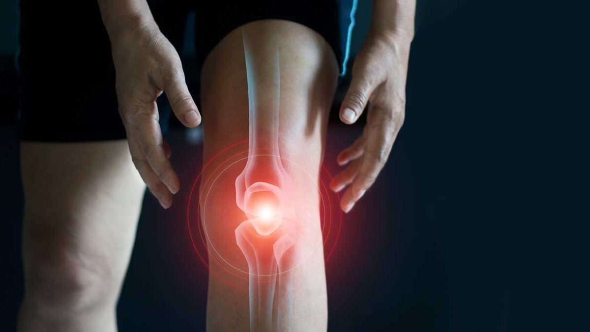 A graphic image showing pain at the knee joint over a picture of a person's leg