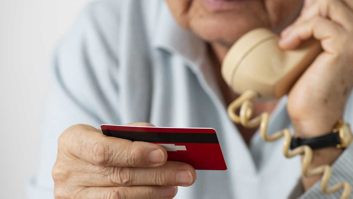 older gentleman on the phone giving his credit card number.