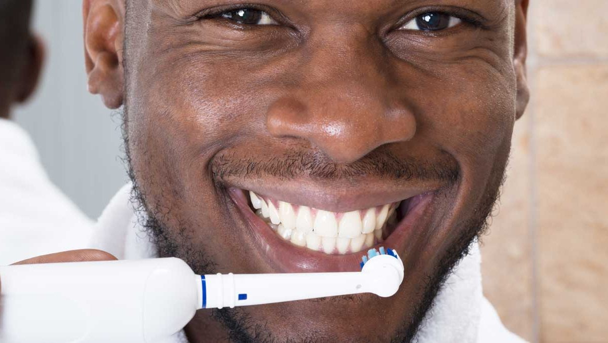 Man smiling at camera, holding an electronic toothbrush