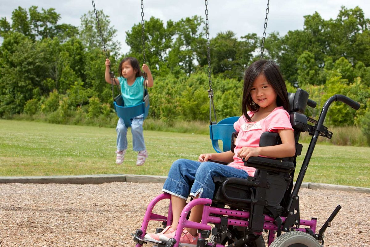 Two children in a playground, one on the swings and one in a manual wheelchair smiling at the camera.