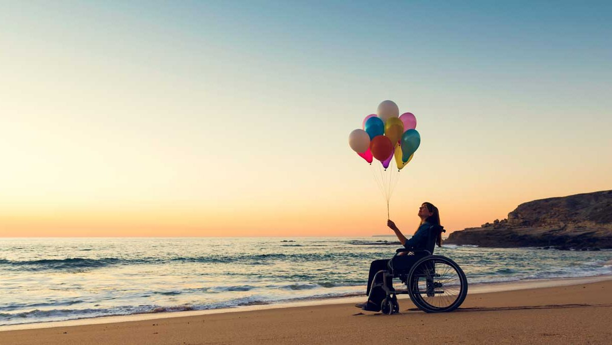 Happy 30th birthday ADA, a woman holding balloons on a beach sitting in a manual wheelchair.