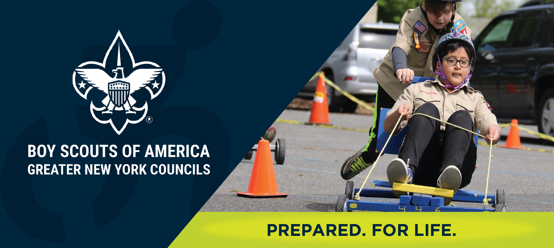 On left side of image, the Boy Scouts of America Greater New York Councils logo. On right side of the image, a Caucasian boy pushes an Asian boy on a homemade cart. They are both wearing Boy Scout uniforms. Underneath, the image reads: PREPARED. FOR LIFE.